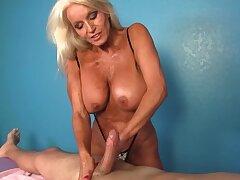 Client receives a handjob by the big-tittied mature masseuse